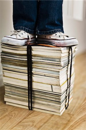Person standing on top of bound stack of books and magazines Stock Photo - Premium Royalty-Free, Code: 695-05770474