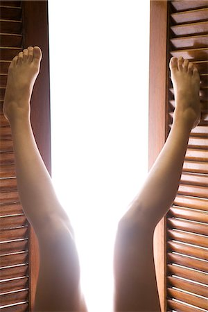 Legs raised opening wooden shutters letting in morning sunlight Stock Photo - Premium Royalty-Free, Code: 695-05770470