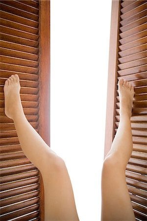 Legs pushing open wooden shutters Stock Photo - Premium Royalty-Free, Code: 695-05770471