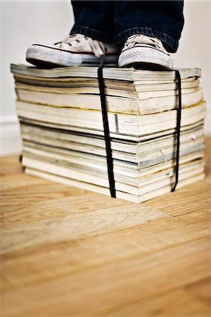 Person standing on top of bound stack of books and magazines Stock Photo - Premium Royalty-Free, Code: 695-05770473