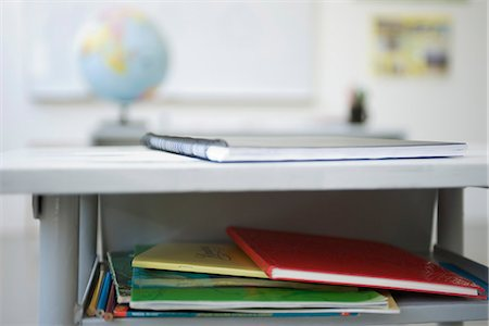school desk - School desk containing stack of books, notebooks Stock Photo - Premium Royalty-Free, Code: 695-05770494