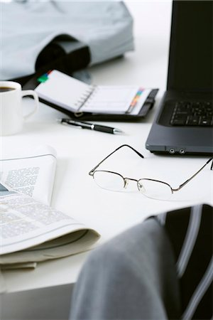 selective focus computer no people - Glasses, newspaper and laptop computer on cluttered desk Stock Photo - Premium Royalty-Free, Code: 695-05770549
