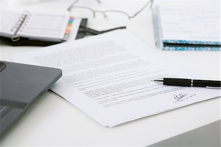 Signed contract on cluttered desk Stock Photo - Premium Royalty-Free, Code: 695-05770551