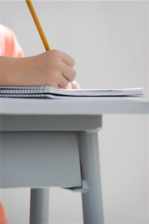 school desk - Young student writing in notebook, cropped Stock Photo - Premium Royalty-Free, Code: 695-05770729