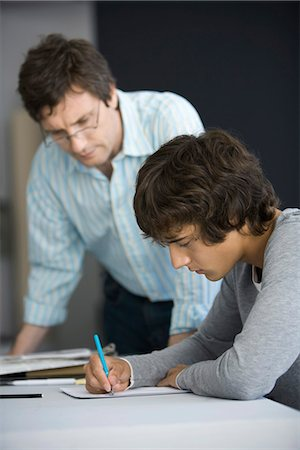 College student working on assignment, teacher assisting Stock Photo - Premium Royalty-Free, Code: 695-05770806