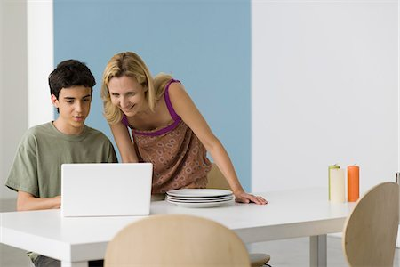 Teenage boy showing mother laptop computer Stock Photo - Premium Royalty-Free, Code: 695-05771305