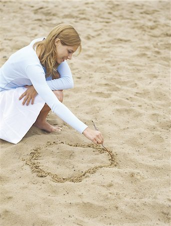 Woman drawing circle in sand, portrait Stock Photo - Premium Royalty-Free, Code: 695-05772442
