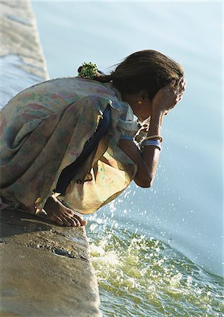 India, Sarkej, girl washing face by river Stock Photo - Premium Royalty-Free, Code: 695-05772504