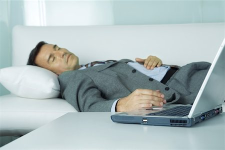 Businessman sleeping on sofa, hand resting on laptop Stock Photo - Premium Royalty-Free, Code: 695-03374841