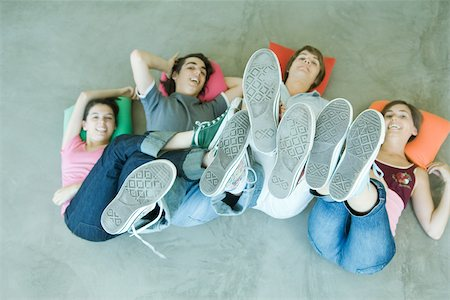 female 16 year old feet - Four teen friends lying on backs on floor, holding up legs, focus on soles of shoes Stock Photo - Premium Royalty-Free, Code: 695-03375664