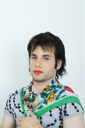 Young man wearing lipstick and scarf around neck, portrait Stock Photo - Premium Royalty-Free, Code: 695-03375784