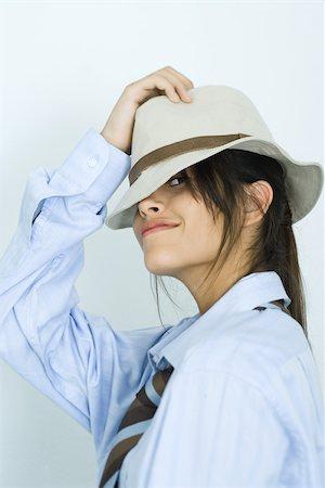 Teen girl wearing shirt, tie and hat, peeking at camera Stock Photo - Premium Royalty-Free, Code: 695-03375803