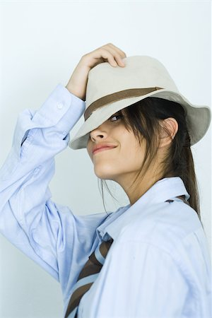 Teen girl wearing shirt, tie and hat, peeking at camera Stock Photo - Premium Royalty-Free, Code: 695-03375803