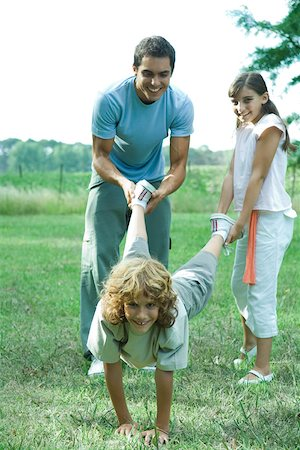 Family outdoors, father and sister holding boy's legs like wheelbarrow Stock Photo - Premium Royalty-Free, Code: 695-03375841
