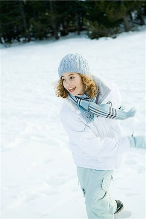 Teenage girl running in snow, looking away, blurred motion Stock Photo - Premium Royalty-Free, Code: 695-03376312