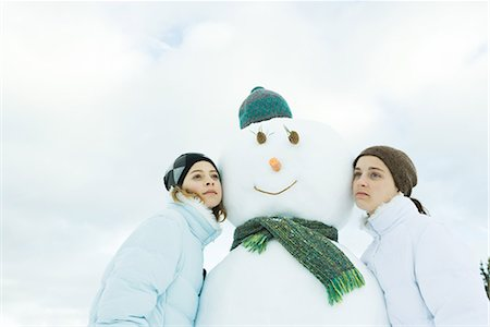 Two teenage girls leaning against snowman, cheek to cheek, looking away Stock Photo - Premium Royalty-Free, Code: 695-03376330