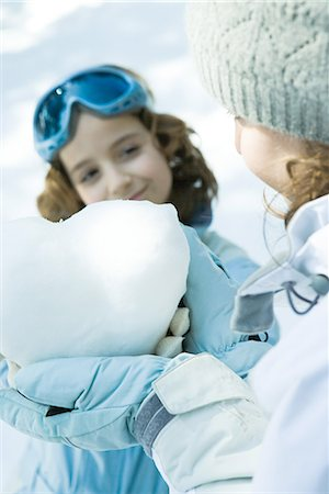 Teenage girl holding heart made of snow, sister smiling in background Stock Photo - Premium Royalty-Free, Code: 695-03376347