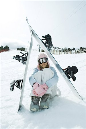 Preteen girl sitting on snow underneath propped up snowboards Stock Photo - Premium Royalty-Free, Code: 695-03376394