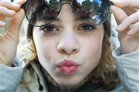 preteen kissing - Preteen girl lifting sunglasses, puckering at camera, close-up Stock Photo - Premium Royalty-Free, Code: 695-03376429