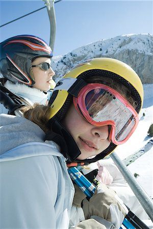 Two young skiers on chair lift, one smiling at camera Stock Photo - Premium Royalty-Free, Code: 695-03376448