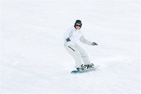 Teenage girl snowboarding on ski slope, full length Stock Photo - Premium Royalty-Free, Code: 695-03376457