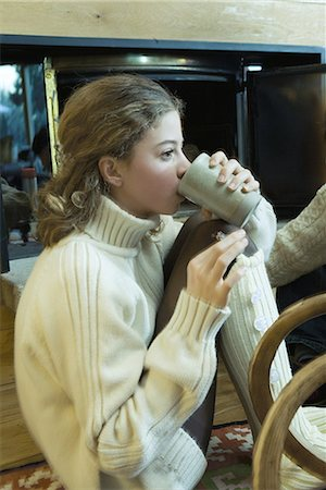 sweater and fireplace - Teen girl drinking hot beverage by fireplace Stock Photo - Premium Royalty-Free, Code: 695-03376557