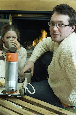 sweater and fireplace - Young man and teen girl drinking hot drinks by fire place Stock Photo - Premium Royalty-Free, Code: 695-03376558