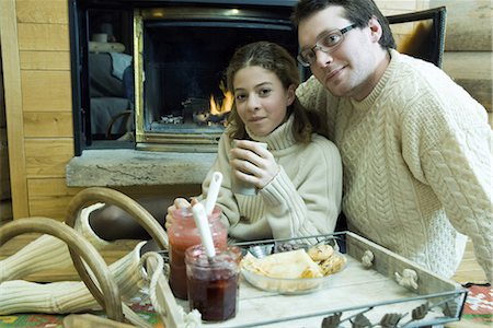 sweater and fireplace - Young man and teen girl drinking hot drinks by fire place Stock Photo - Premium Royalty-Free, Code: 695-03376559