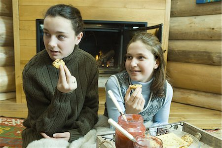 sweater and fireplace - Teen girls having snack by fire place Stock Photo - Premium Royalty-Free, Code: 695-03376560