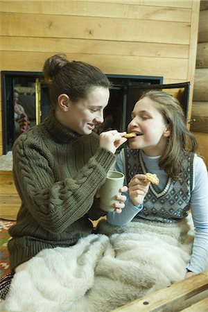 sweater and fireplace - Teen girls having snack by fire place Stock Photo - Premium Royalty-Free, Code: 695-03376561