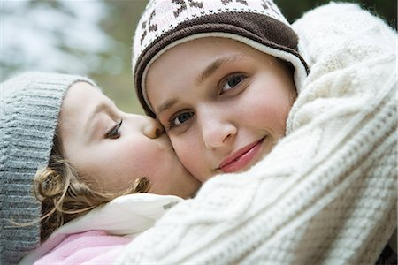 preteen kissing - Teenage girl smiling at camera, sister kissing her on cheek, portrait Stock Photo - Premium Royalty-Free, Code: 695-03376888