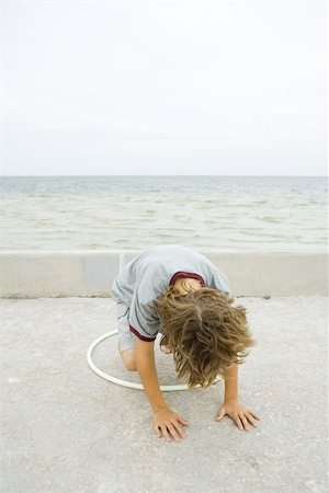 Boy crouching on all fours, playing with plastic hoop, head down Stock Photo - Premium Royalty-Free, Code: 695-03377173