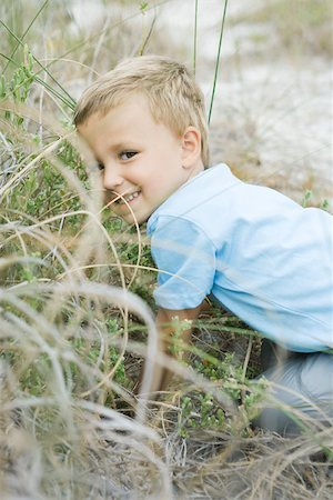 Young boy crouching in tall grass, looking over shoulder at camera Stock Photo - Premium Royalty-Free, Code: 695-03377250