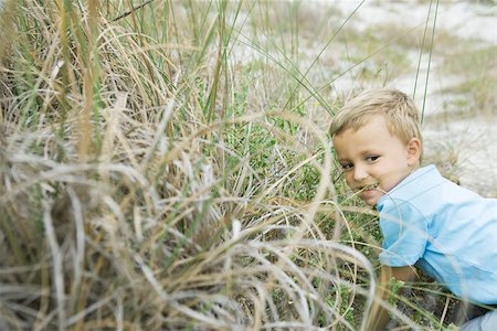 Young boy crouching in tall grass, looking away Stock Photo - Premium Royalty-Free, Code: 695-03377251