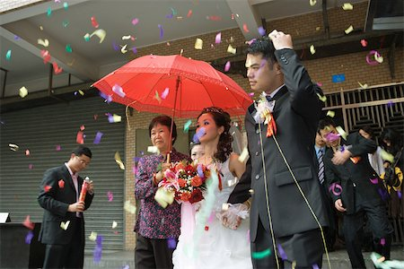 Chinese wedding, bride and groom leaving under confetti, bride covered by red parasol Stock Photo - Premium Royalty-Free, Code: 695-03377441