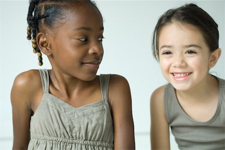 Two girls smiling, side by side, one looking at the other Stock Photo - Premium Royalty-Free, Code: 695-03377513