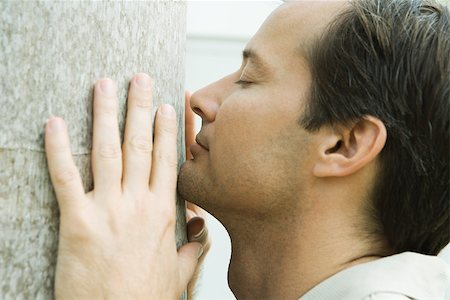 smelly - Man smelling tree trunk, eyes closed, side view, close-up Stock Photo - Premium Royalty-Free, Code: 695-03377738