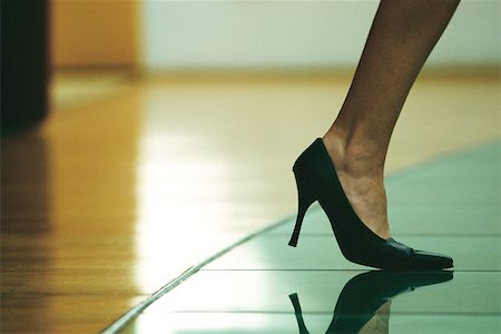Woman walking in high heels, cropped view of foot Stock Photo - Premium Royalty-Free, Code: 695-03378125