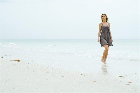 forward - Woman in sundress walking at the beach, looking away Stock Photo - Premium Royalty-Free, Code: 695-03378305