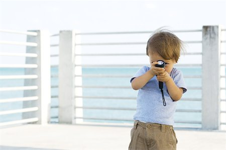shy baby - Toddler boy standing outdoors, hiding behind flashlight, peeking at camera Stock Photo - Premium Royalty-Free, Code: 695-03378550