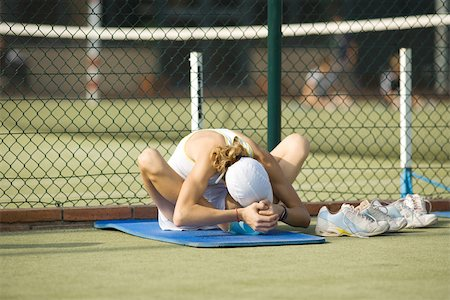 Teenage girl sitting on mat on the ground, bending over, stretching Stock Photo - Premium Royalty-Free, Code: 695-03378571