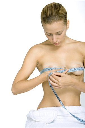 Nude woman measuring breasts with measuring tape, looking down Stock Photo - Premium Royalty-Free, Code: 695-03379046