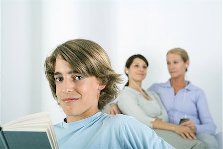 Teenage boy holding book, smiling at camera, women listening to MP3 player in background Stock Photo - Premium Royalty-Free, Code: 695-03379187