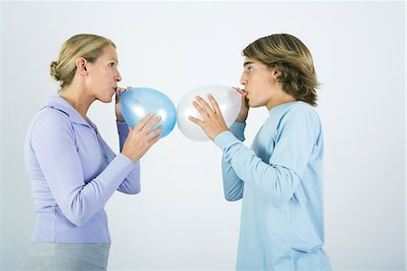 Mother and teen son standing face to face, inflating balloons, side view Stock Photo - Premium Royalty-Free, Code: 695-03379189