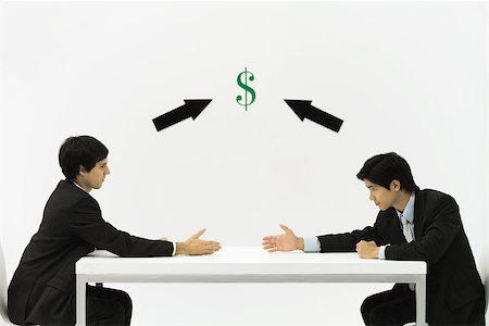 Two businessmen face to face, reaching to shake hands, dollar sign and arrows between them Stock Photo - Premium Royalty-Free, Code: 695-03379494