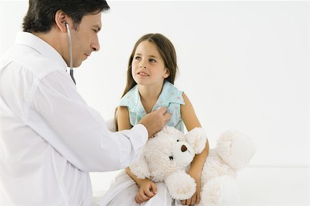 Pediatrician listening to girl's heart with stethoscope, girl holding teddy bear Stock Photo - Premium Royalty-Free, Code: 695-03379547