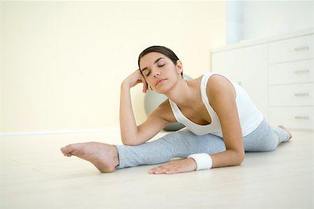 Woman doing split, holding head, eyes closed Stock Photo - Premium Royalty-Free, Code: 695-03379948