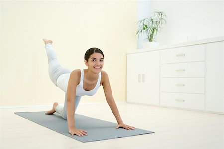 Woman down on all fours, exercising, smiling at camera Stock Photo - Premium Royalty-Free, Code: 695-03379943