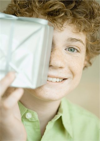 silver box - Boy holding up present in front of face Stock Photo - Premium Royalty-Free, Code: 695-03373751