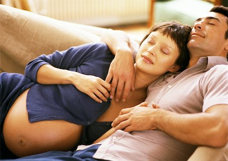 pregnant couple couch - Pregnant woman leaning head on man's chest, on sofa Stock Photo - Premium Royalty-Free, Code: 695-03384058